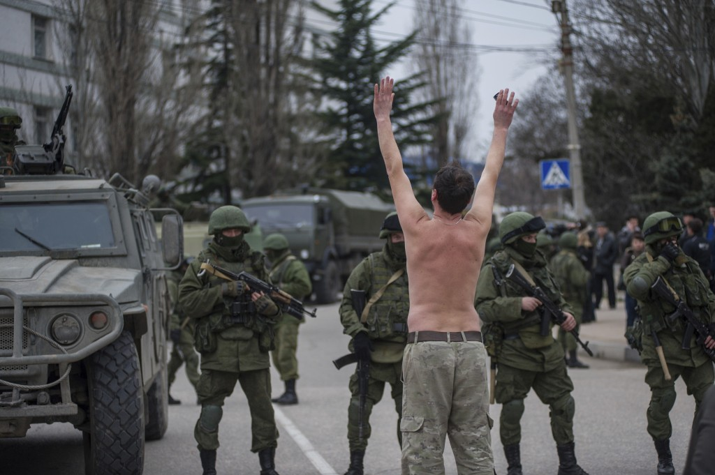 FILE - In this Saturday, March 1, 2014 file photo, a Ukrainian man stands in protest in front of gunmen in unmarked uniforms as they stand guard in ba...