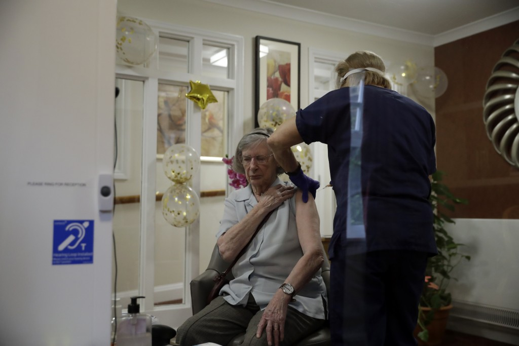 Care home resident Jean Allen, aged 91, is seen through a viewing screen installed for residents to safely receive visits from family members, as she ...