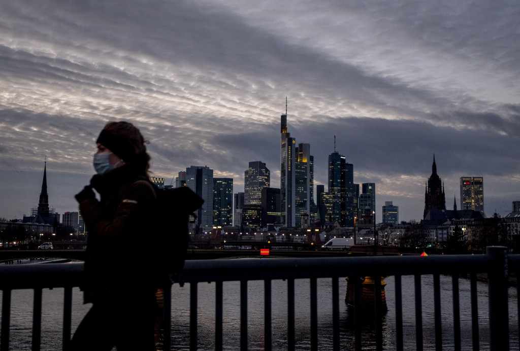 A woman wearing a face mask passes the skyline in Frankfurt, Germany, Wednesday, Jan. 13, 2021. (AP Photo/Michael Probst)