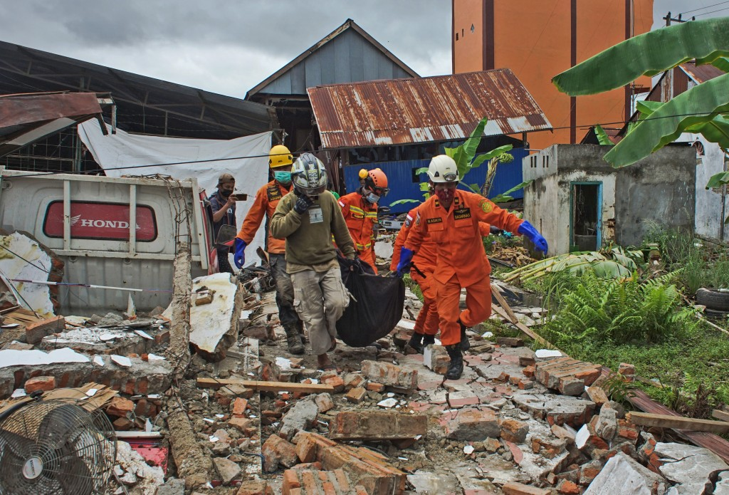 Rescuers carry a body bag containing a victim of an earthquake in Mamuju, West Sulawesi, Indonesia, Friday, Jan. 15, 2021. A strong, shallow earthquak...