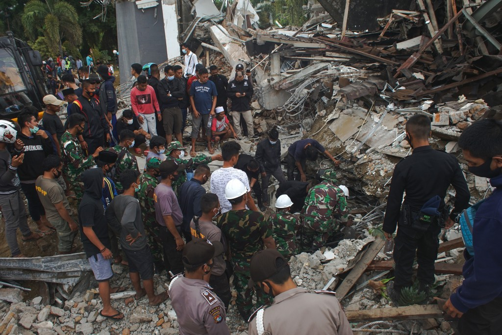 Rescuers search for survivors at the ruin of a government building collapsed during an earthquake in Mamuju, West Sulawesi, Indonesia, Friday, Jan. 15...
