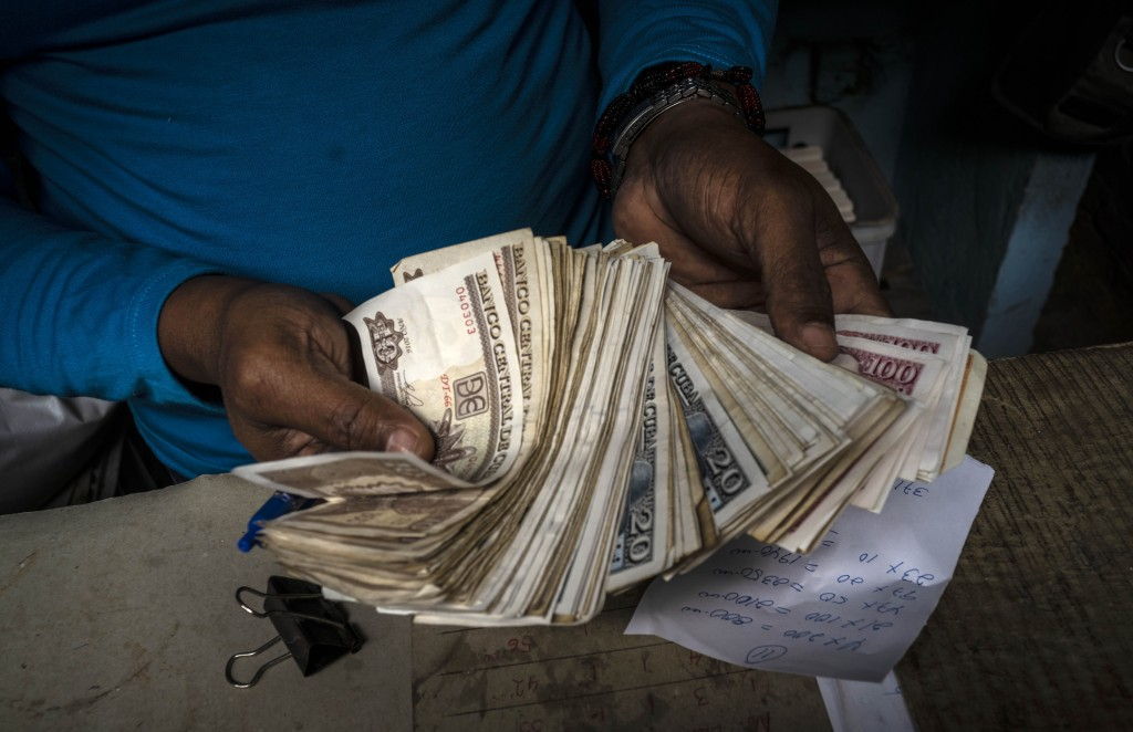 FILE - In this Dec. 11, 2020 file photo, a worker shows a wad of Cuban pesos in Havana, Cuba, Friday, Dec. 11, 2020. In 2021, the government is implem...