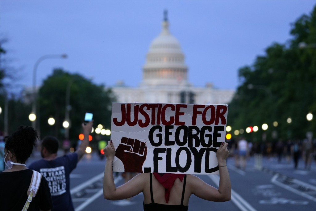 FILE - In this May 29, 2020, file photo, Demonstrators walk along Pennsylvania Avenue as they protest the death of George Floyd, a black man who died ...