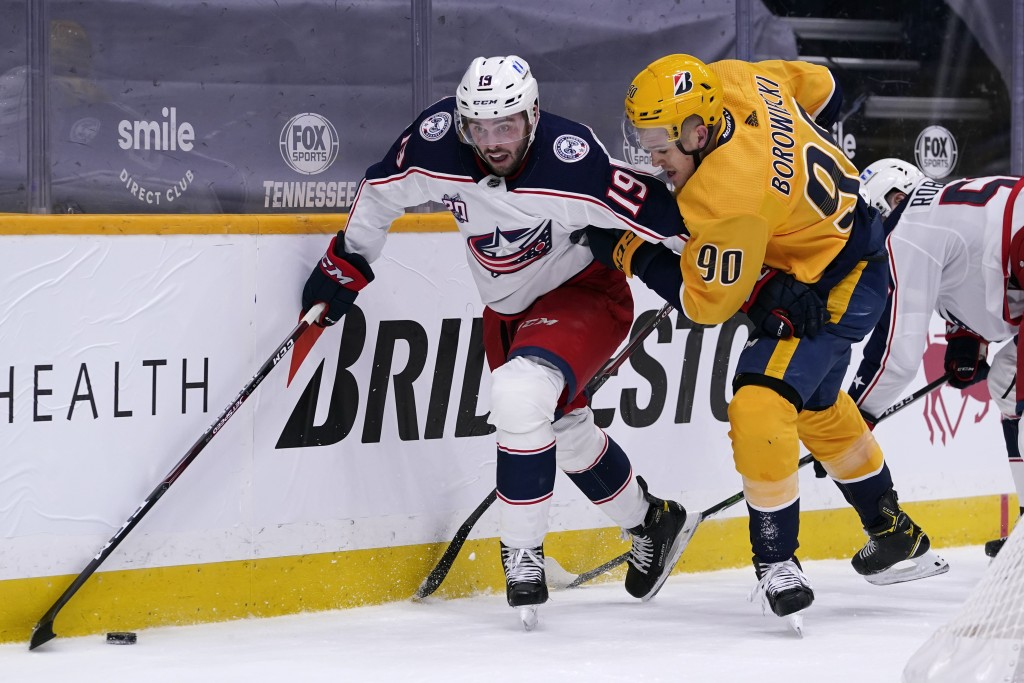 Columbus Blue Jackets center Liam Foudy (19) and Nashville Predators defenseman Mark Borowiecki (90) battle for the puck in the first period of an NHL...