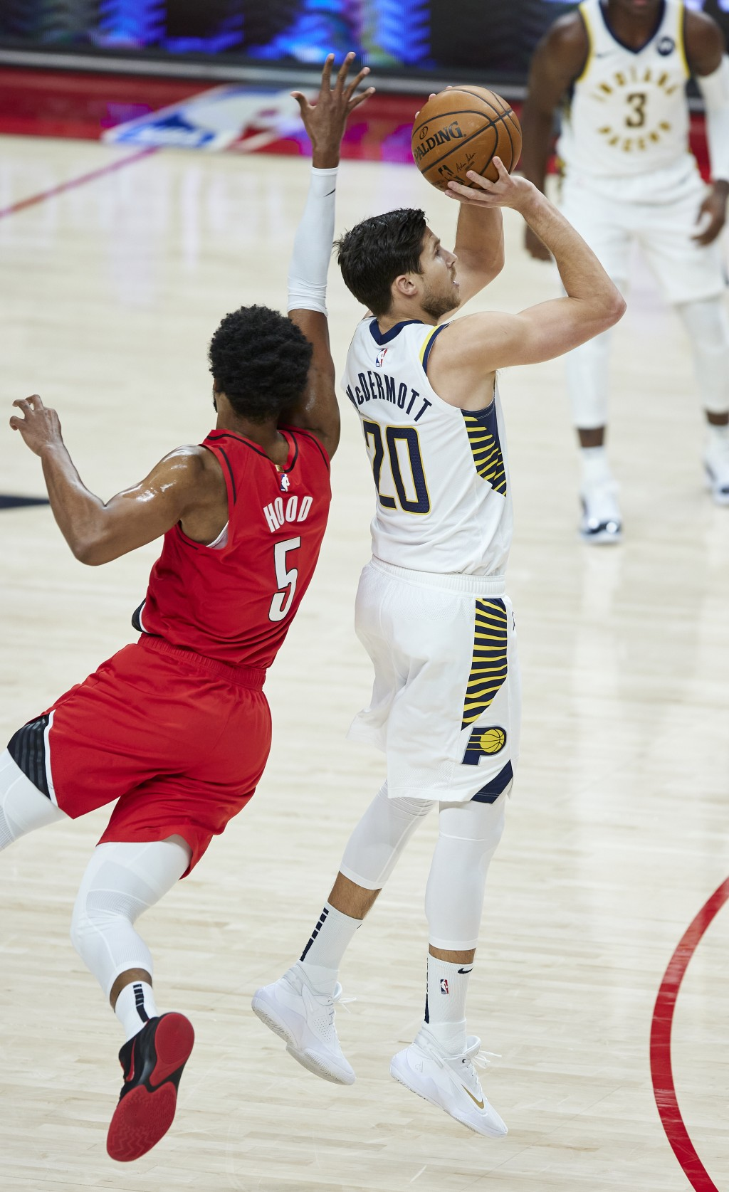 Indiana Pacers forward Doug McDermott, right, shoots a three-point basket in front of Portland Trail Blazers guard Rodney Hood during the first half o...