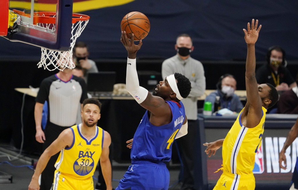 Denver Nuggets forward Paul Millsap, center, drives to the rim as Golden State Warriors guard Stephen Curry, left, and forward Andrew Wiggins defend i...