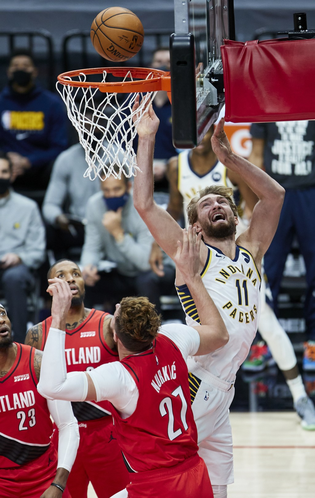 Indiana Pacers forward Domantas Sabonis, right, shoots over Portland Trail Blazers center Jusuf Nurkic during the first half of an NBA basketball game...