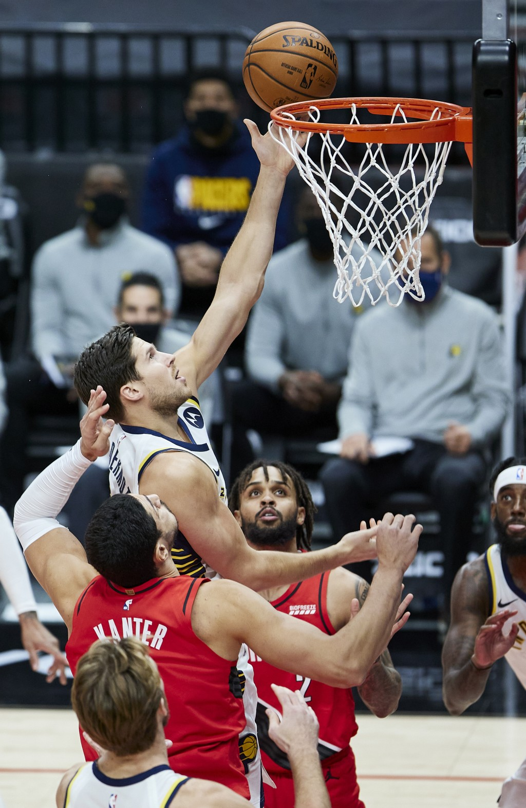 Indiana Pacers forward Doug McDermott, center, shoots between Portland Trail Blazers center Enes Kanter, left, and guard Gary Trent Jr. during the fir...