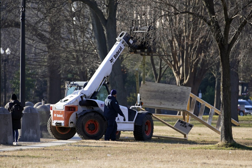 FILE - In this Jan. 7, 2021, file photo, crew remove a scaffolding near the U.S. Capitol that had a noose hanging from it the day before in Washington...