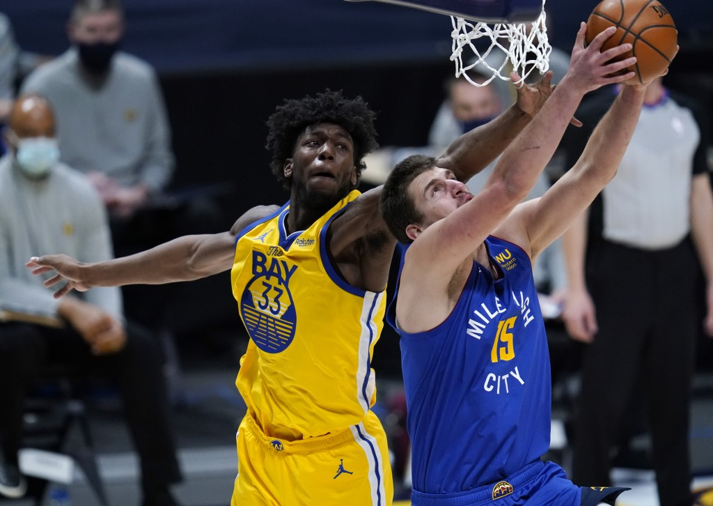 Denver Nuggets center Nikola Jokic, front, drives to the rim for a reverse dunk basket past Golden State Warriors center James Wiseman in the first ha...