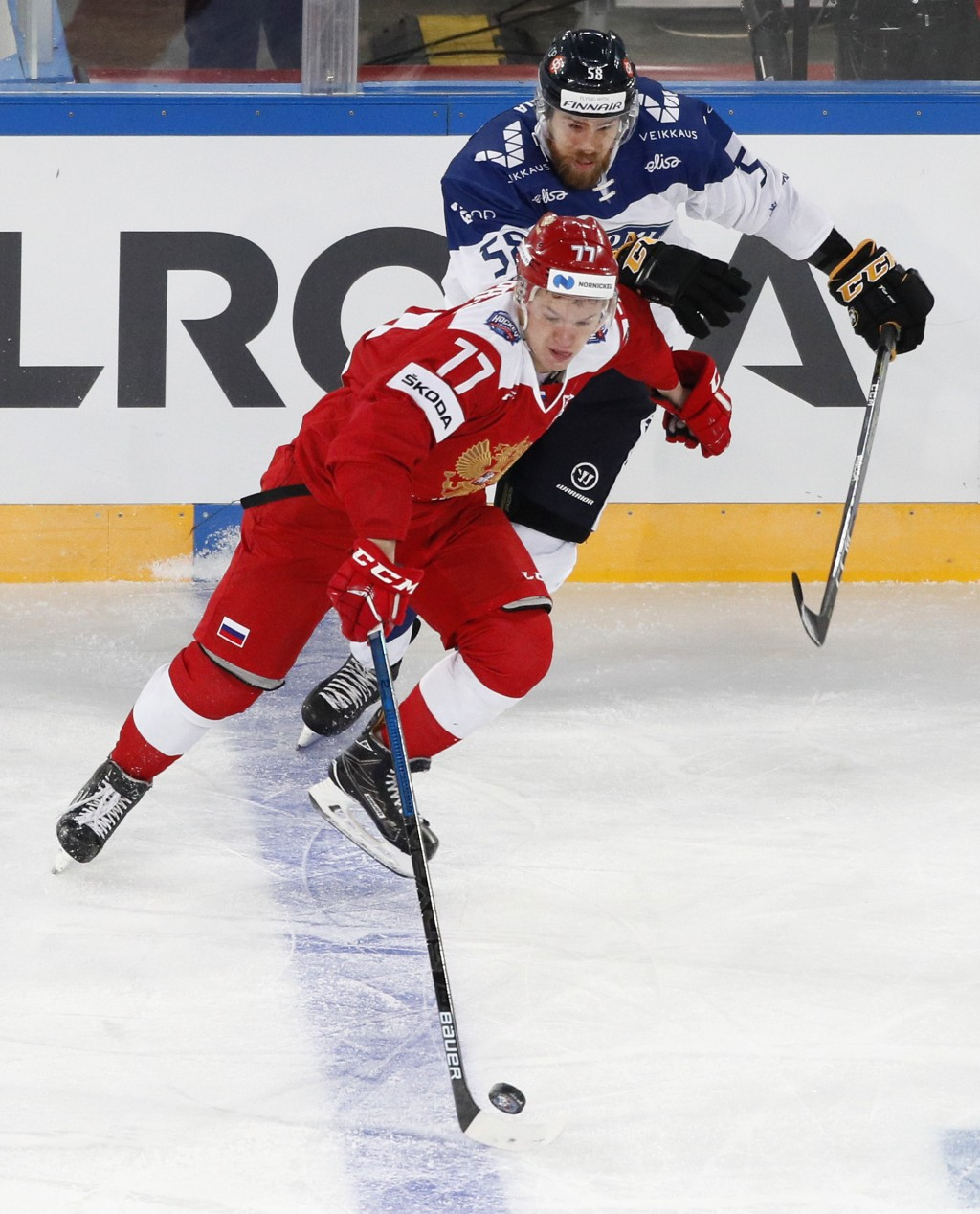 FILE - In this Sunday, Dec. 16, 2018, file photo, Russia's Kirill Kaprizov (77) battles Finland's Jani Hakanpaa (58) during the Channel One Cup ice ho...