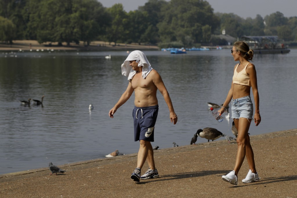 FILE - In this Wednesday, Aug. 12, 2020 file photo, a man keeps cool with a shirt over his head as he walks alongside The Serpentine in Hyde Park in L...