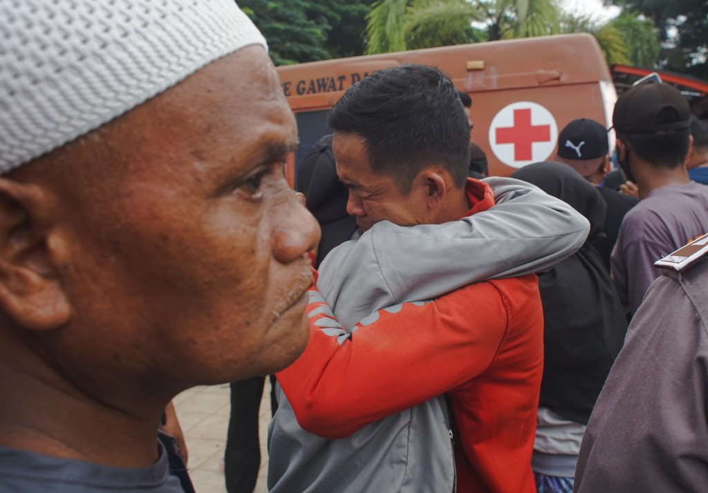 Indonesian men comfort each other following an earthquake in Mamuju, West Sulawesi, Indonesia, Friday, Jan. 15, 2021. A strong, shallow earthquake sho...