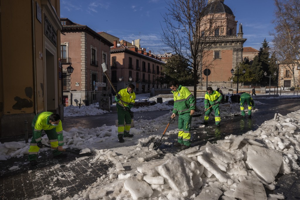 Municipality workers remove ice from a street in Madrid, Spain, Thursday, Jan. 14, 2021. With piles of ice and snow still covering most streets of Mad...