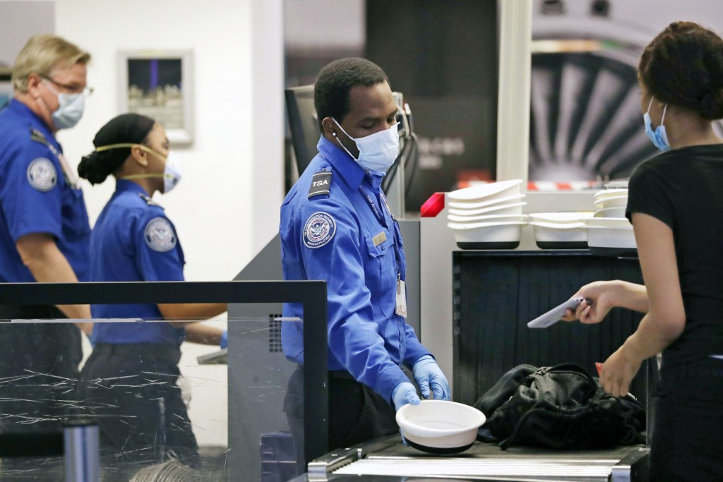 TSA officers wear protective masks at a security screening area at Seattle-Tacoma International Airport Monday, May 18, 2020, in SeaTac, Wash. Airline...