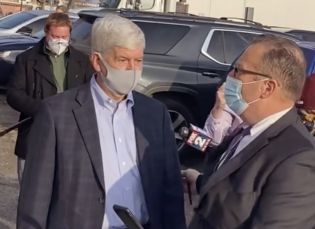 In this image taken from video, former Michigan Gov. Rick Snyder, left, with his lawyer, Brian Lennon, leave Genesee County Court in Flint, Mich., Thu...