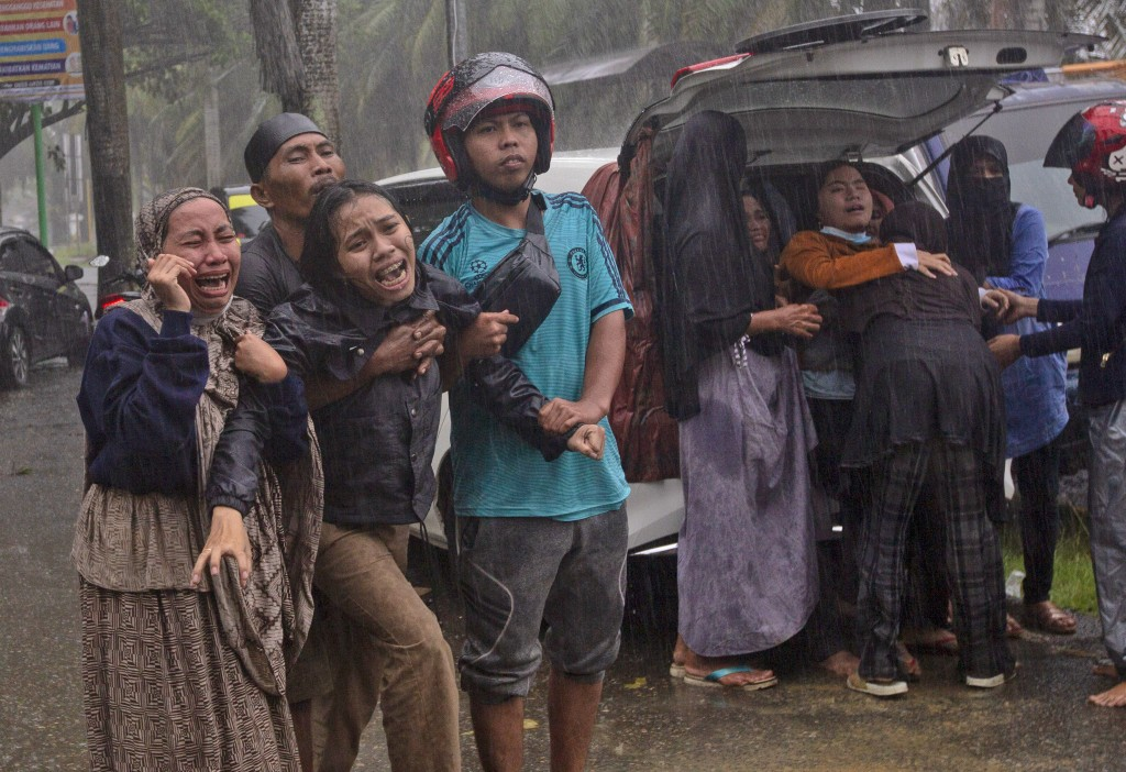 People react as the body of a relative is retrieved from the ruin of a building at an area affected by an earthquake in Mamuju, West Sulawesi, Indones...