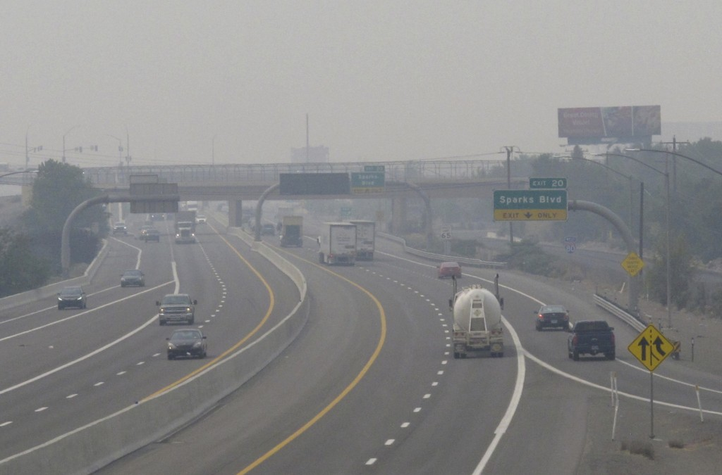 FILE - In this Wednesday, Aug. 19, 2020. file photo, smoke from California wildfires up to 200 miles away obscures the view of traffic traveling on In...
