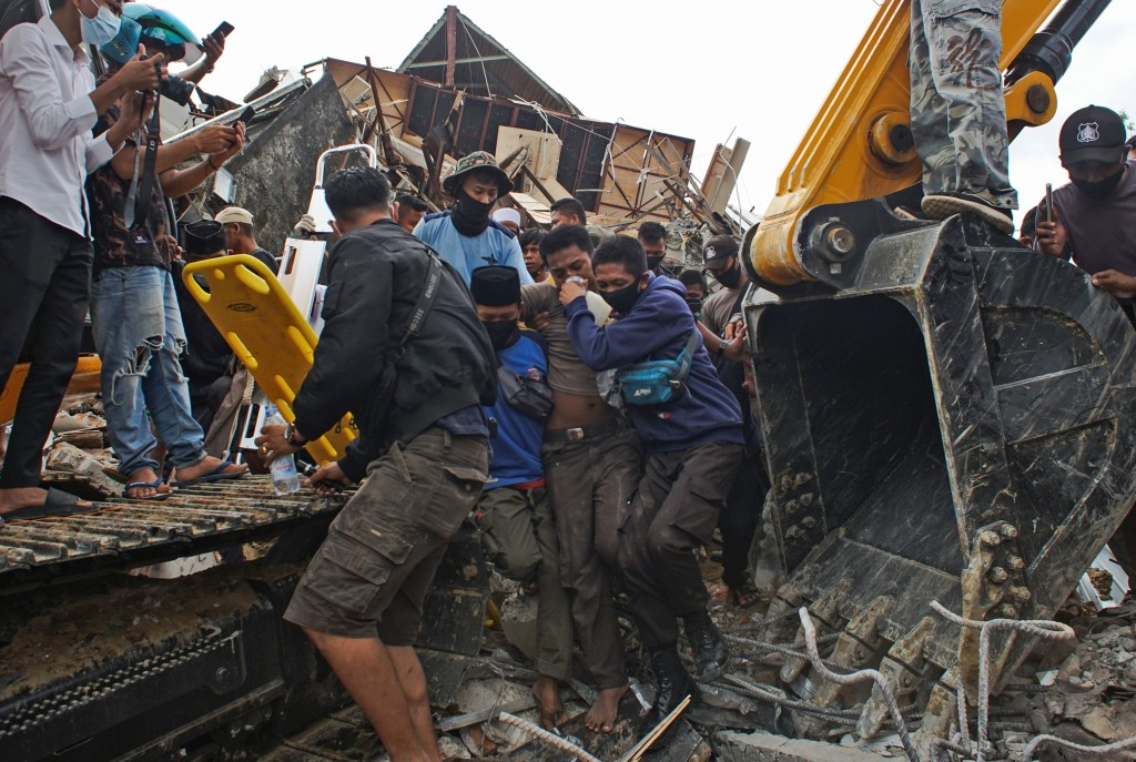 Rescuers assist a survivor pulled out from the ruin of a government building collapsed during an earthquake in Mamuju, West Sulawesi, Indonesia, Frida...
