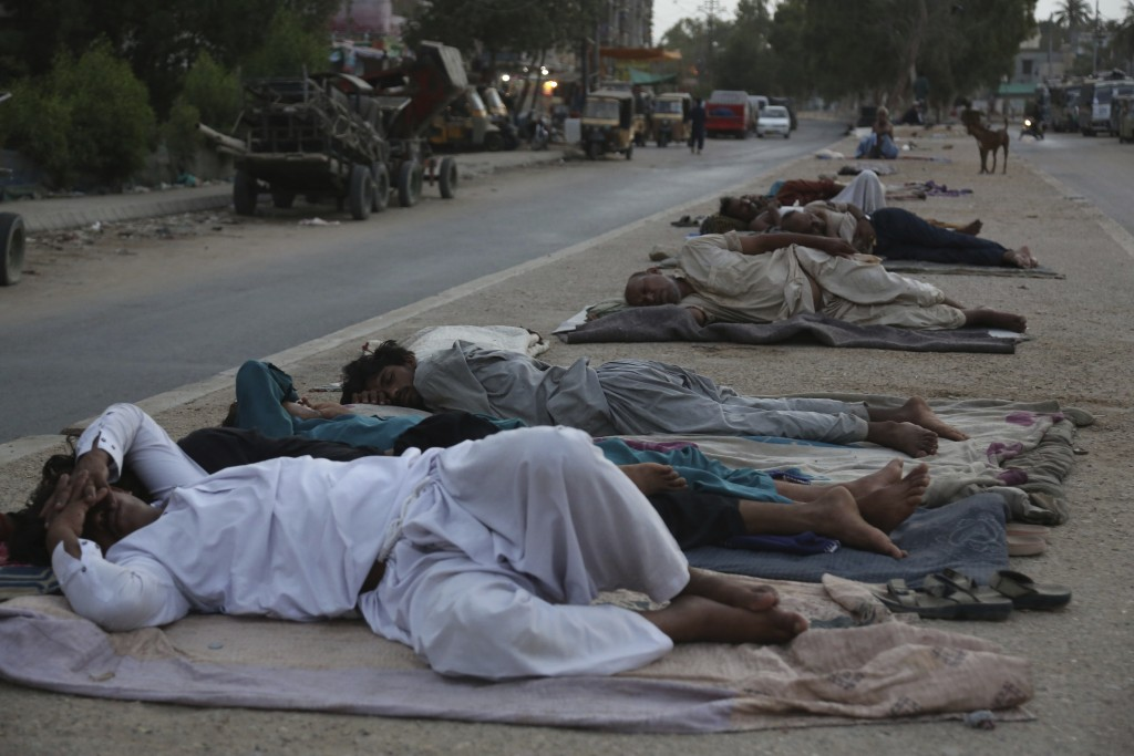 FILE - In this Thursday, June 18, 2020 file photo, vendors and rickshaw drivers sleep in the open early on a hot summer morning in Karachi, Pakistan, ...