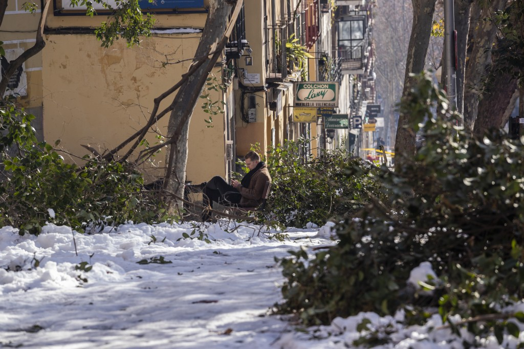 Surrounded of broken tree branches, a man sits on a bench in Madrid, Spain, Thursday, Jan. 14, 2021. With piles of ice and snow still covering most st...