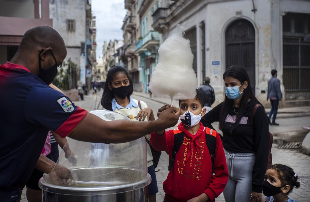 FILE - In this Jan. 11, 2021 file photo, people wearing masks as a precaution against the spread of the new coronavirus wait for their turn to buy cot...