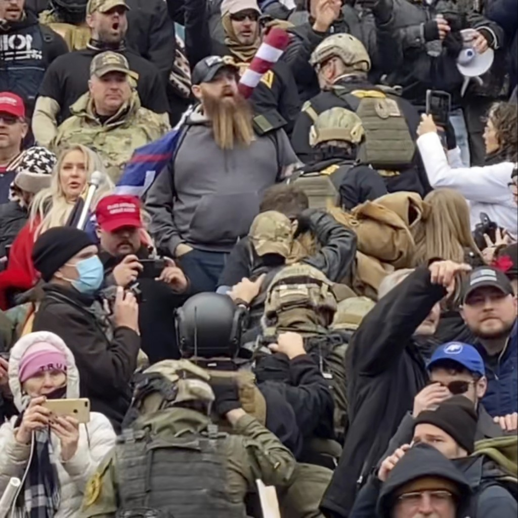 In this Jan. 6, 2021 image from video provided by Robyn Stevens Brody, a line of men wearing helmets and olive drab body armor walk up the marble stai...