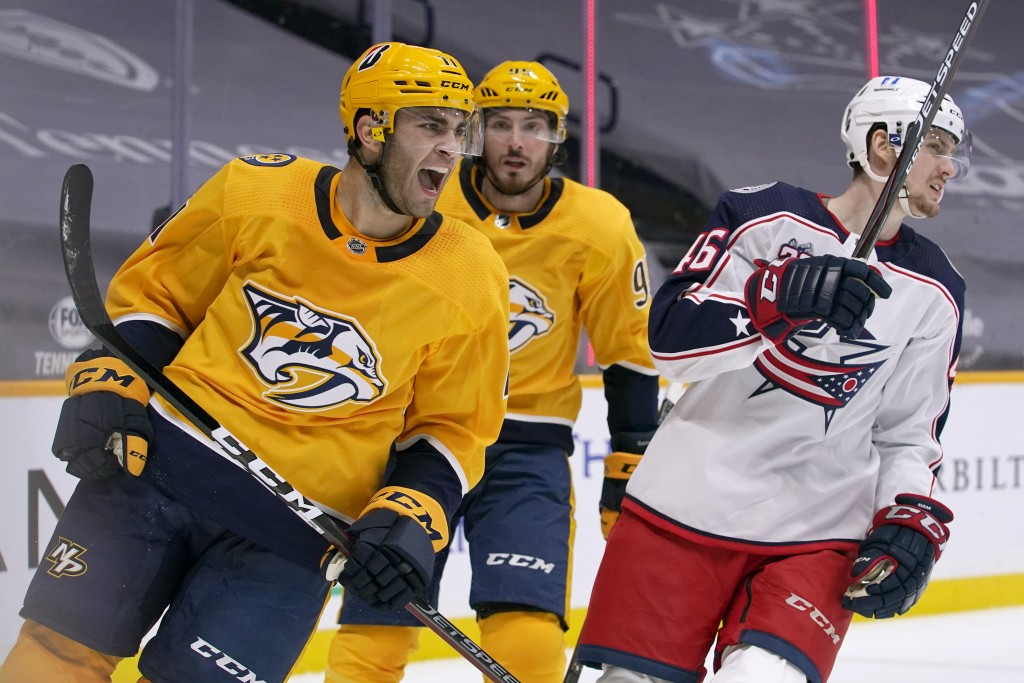 Nashville Predators center Luke Kunin, left, celebrates after scoring a goal against the Columbus Blue Jackets in the second period of an NHL hockey g...