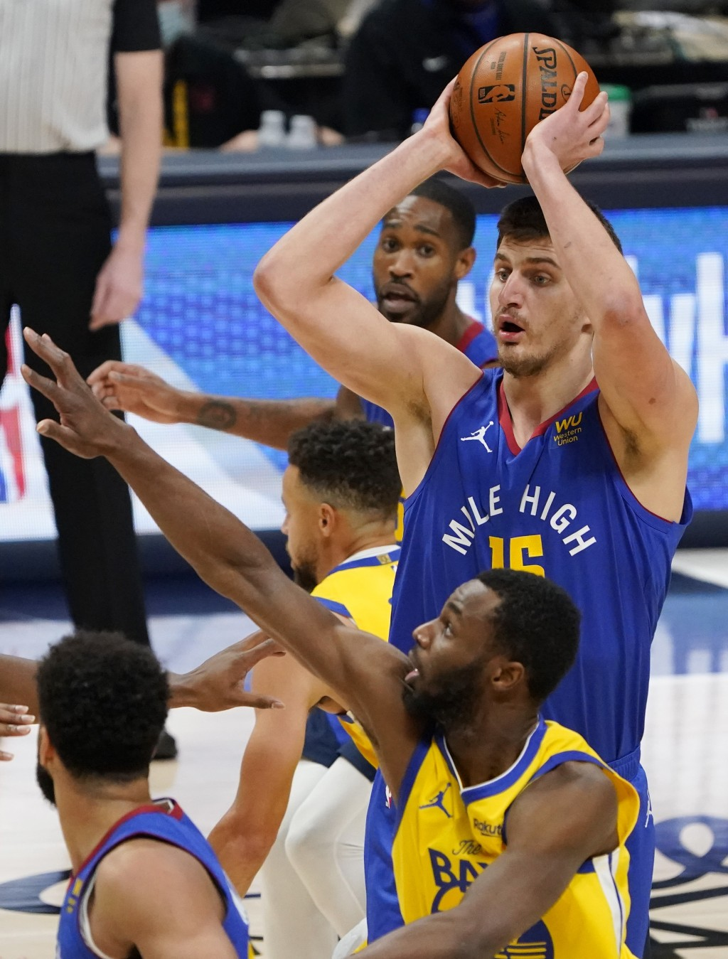 Denver Nuggets center Nikola Jokic, back, looks to pass the ball as Golden State Warriors forward Andrew Wiggins defends in the first half of an NBA b...
