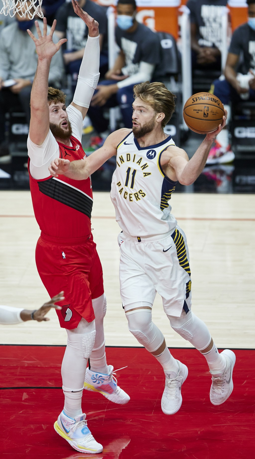 Indiana Pacers forward Domantas Sabonis, right, passes the ball away from Portland Trail Blazers center Jusuf Nurkic during the first half of an NBA b...