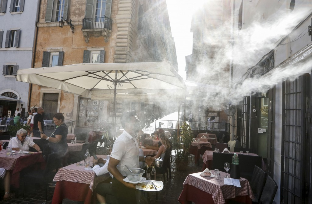FILE - In this Friday, July 31, 2020 file photo, a fan sprays water mist as customers sit outside a cafe in downtown Rome during a heat wave with temp...