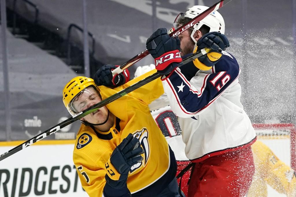 Nashville Predators defenseman Matt Benning (5) gets a stick to the nose as he collides with Columbus Blue Jackets center Liam Foudy (19) in the third...