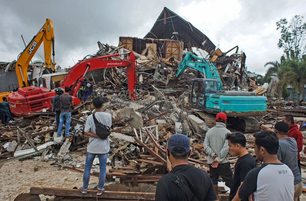 Rescuers search for survivors at the ruin of a local government building collapsed during an earthquake in Mamuju, West Sulawesi, Indonesia, Friday, J...