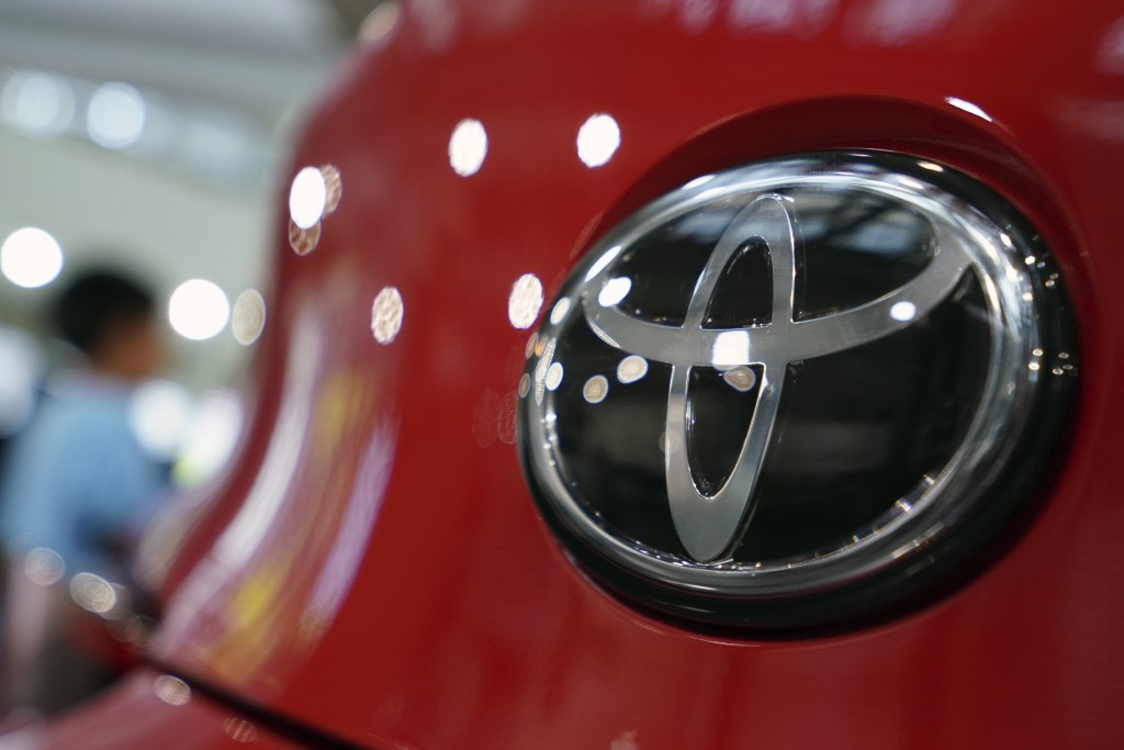FILE - In this Aug. 2, 2019, file, photo, people walk by the logo of Toyota at a show room in Tokyo. Toyota will pay $180 million to settle U.S. gover...