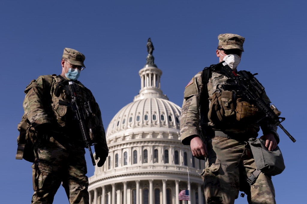 Members of the National Guard walk past the Dome of the Capitol Building on Capitol Hill in Washington, Thursday, Jan. 14, 2021. (AP Photo/Andrew Harn...