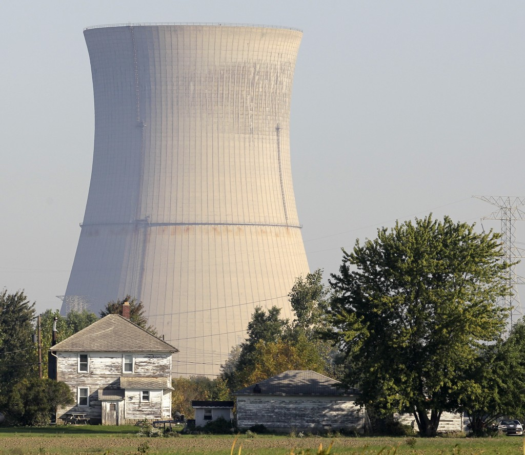 FILE-In this Oct. 5, 2011 file photo, the cooling tower of the Davis-Besse Nuclear Power Station looms over an adjacent farm in Oak Harbor, Ohio. Acro...