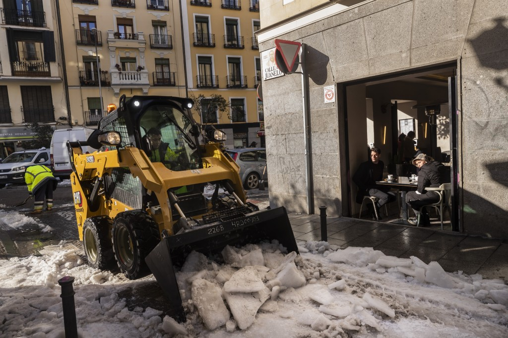 Workers remove ice from a street in Madrid, Spain, Thursday, Jan. 14, 2021. With piles of ice and snow still covering most streets of Madrid, the Span...
