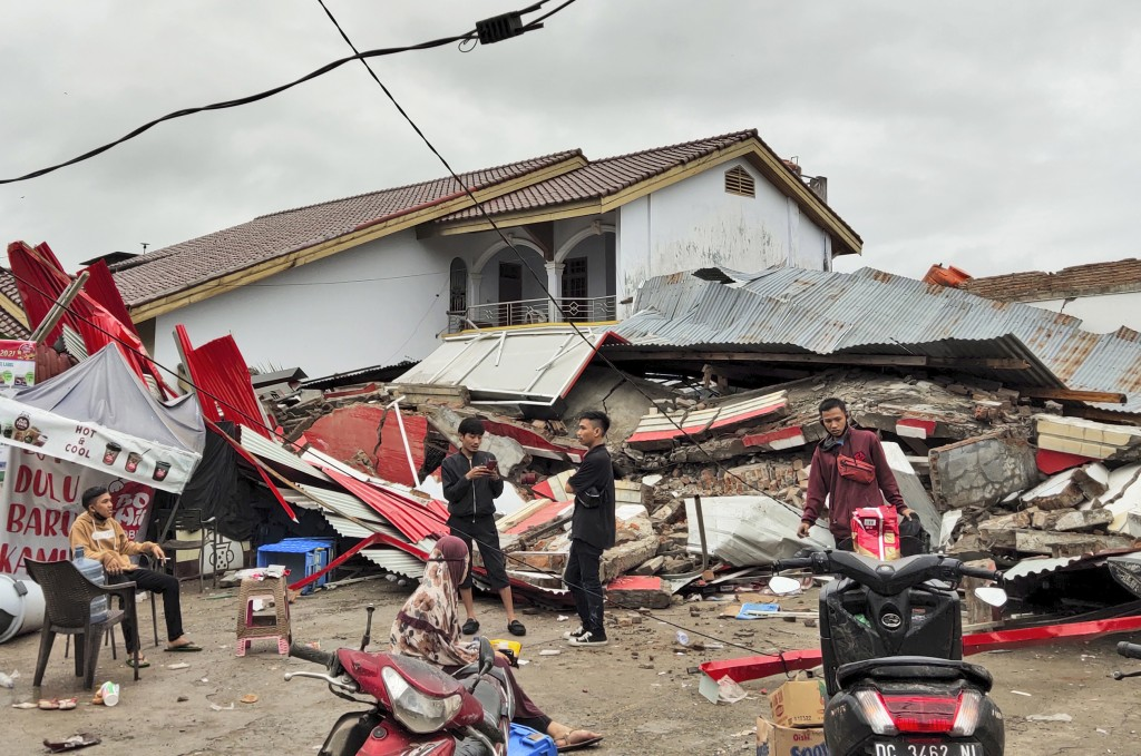 Residents stand near a building flattened by an earthquake in Mamuju, West Sulawesi, Indonesia, Friday, Jan. 15, 2021. A strong, shallow earthquake sh...