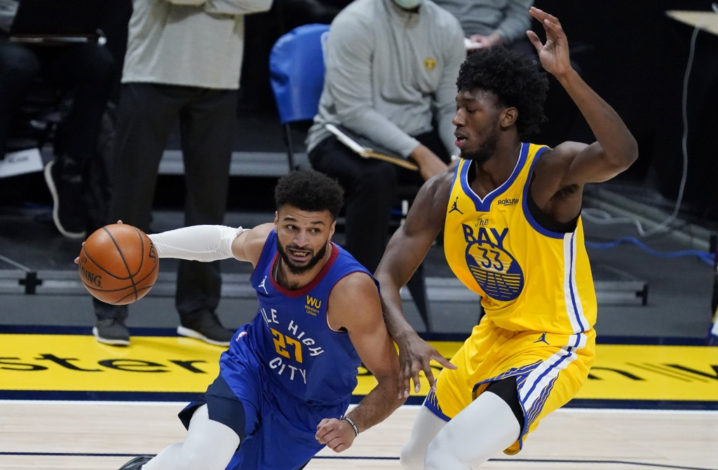 Denver Nuggets guard Jamal Murray, left, drives past Golden State Warriors center James Wiseman in the first half of an NBA basketball game Thursday, ...