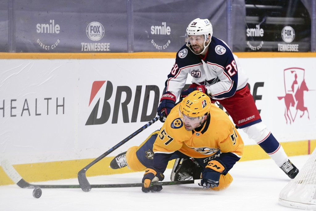Nashville Predators defenseman Dante Fabbro (57) and Columbus Blue Jackets right wing Oliver Bjorkstrand (28) battle for the puck in the first period ...