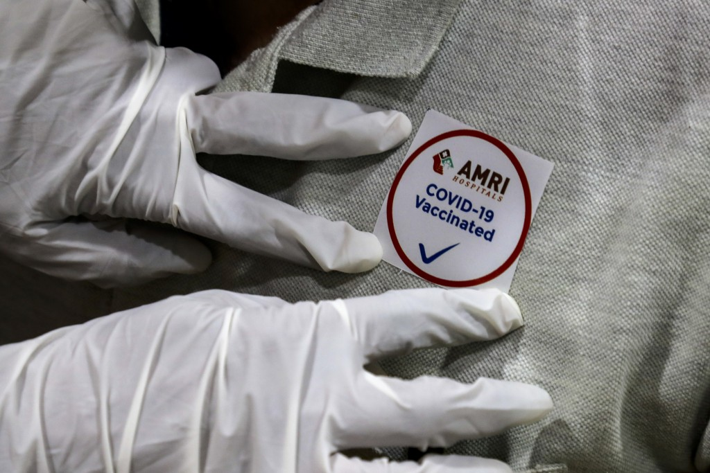A hospital staff puts a badge on the chest of a colleague after being administered COVID-19 vaccine at a hospital in Kolkata, India, Saturday, Jan. 16...