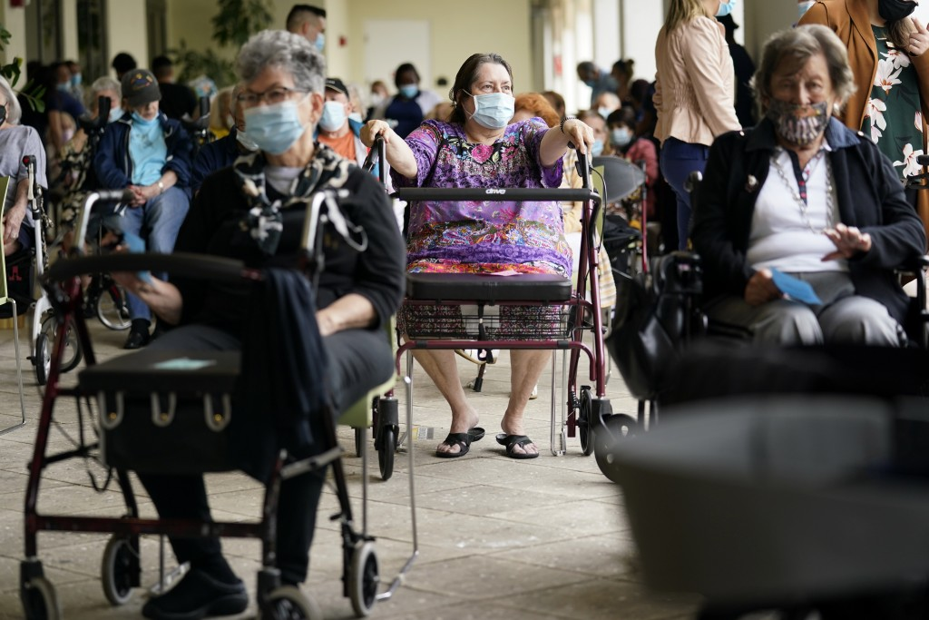 FILE - In this Jan. 12, 2021, file photo Resident Sabeth Ramirez, 80, center, waits in line with others for the Pfizer-BioNTech COVID-19 vaccine at th...