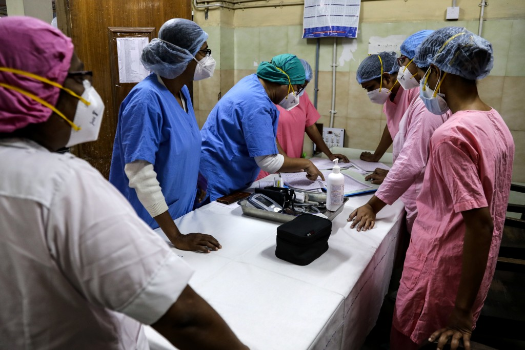 Hospital staff goes through the documents prior to COVID-19 vaccination drive at a hospital in Kolkata, India, Saturday, Jan. 16, 2021. India started ...