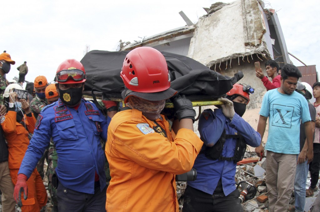 Rescuers carry the body of an earthquake victim retrieved from the ruin of a building damaged by an earthquake in Mamuju, West Sulawesi, Indonesia, Sa...