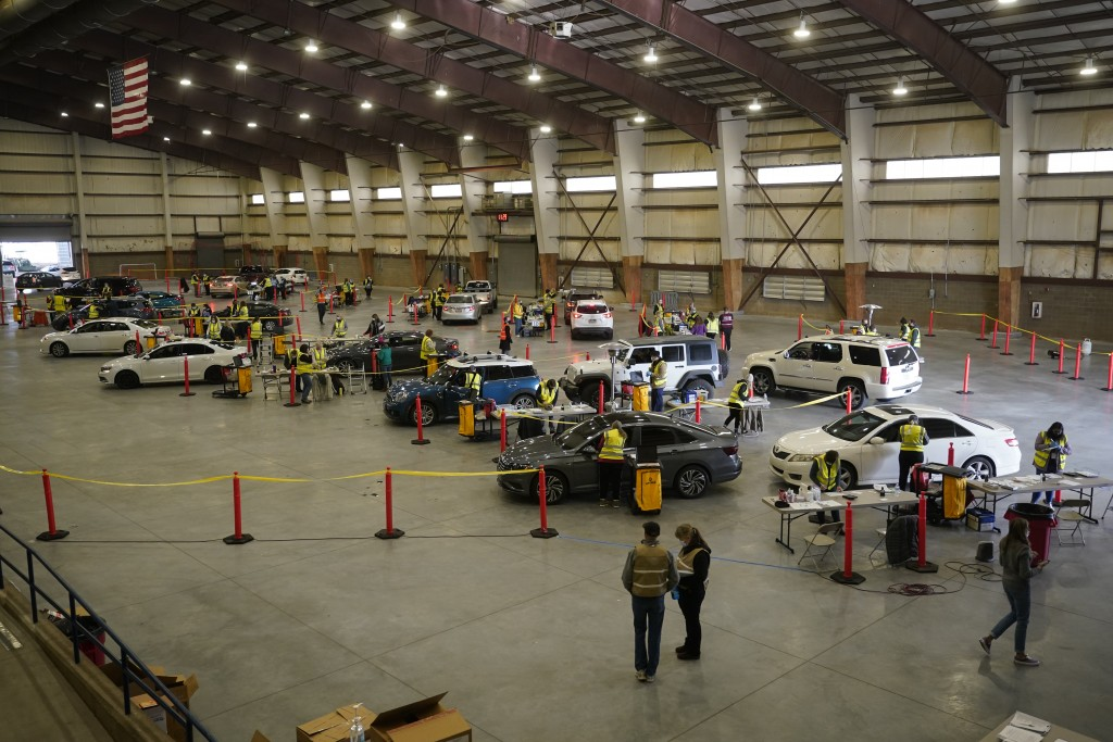 FILE - In this Jan. 12, 2021, file photo, cars pull in to nursing stations for the COVID-19 vaccine roll out at the Davis County Legacy Center in Farm...