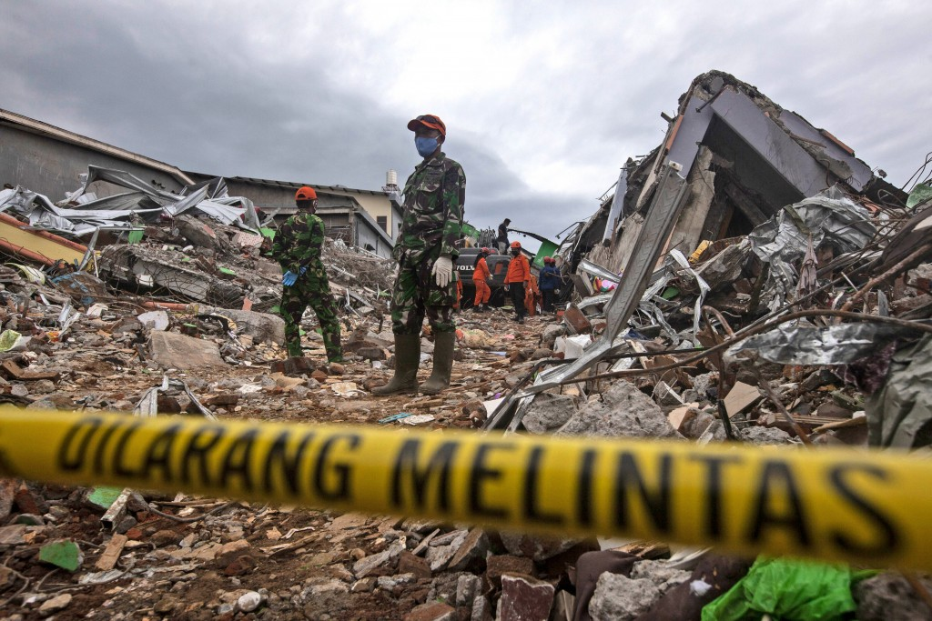Rescuers search for victims at the ruin of a building flattened during an earthquake in Mamuju, West Sulawesi, Indonesia, Saturday, Jan. 16, 2021. Dam...