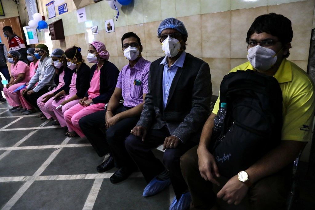 First batch of health workers wait for their turn to get vaccinated at a hospital in Kolkata, India, Saturday, Jan. 16, 2021. India started inoculatin...