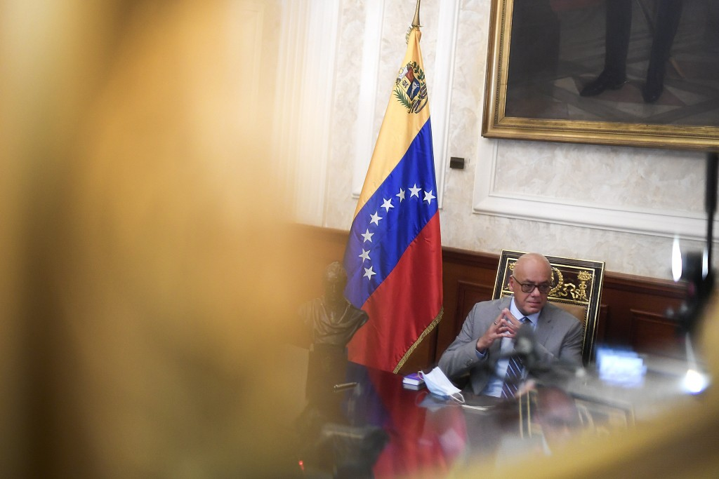 Reflected in a mirror, National Assembly President Jorge Rodriguez gives an interview at Congress in Caracas, Venezuela, Friday, Jan. 15, 2021. Rodrig...