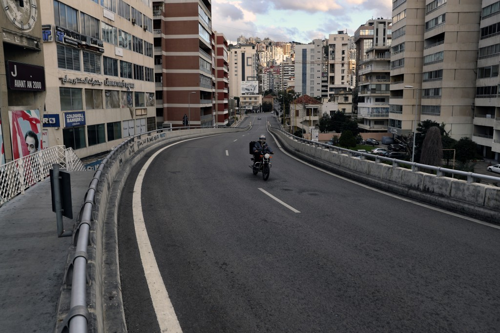 A food deliveryman on a scooter moves on an empty street during a lockdown aimed at curbing the spread of the coronavirus, in Beirut, Lebanon, Friday,...