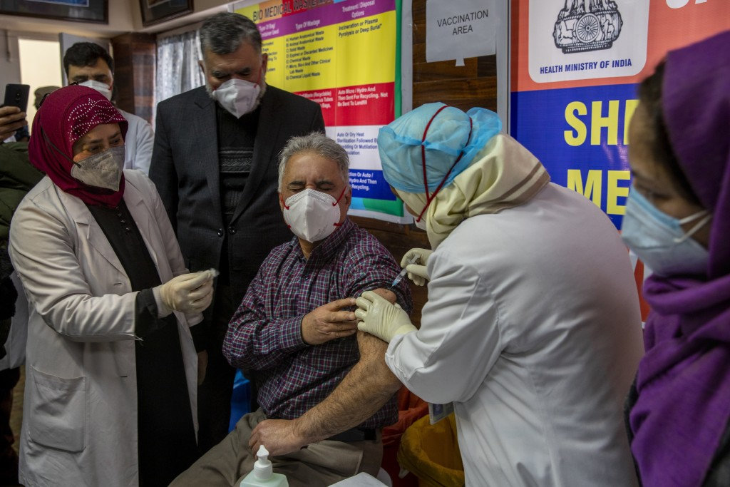 A Kashmiri doctor receives a COVID-19 vaccine at a government Hospital in Srinagar, Indian controlled Kashmir, Saturday, Jan. 16, 2021. India started ...